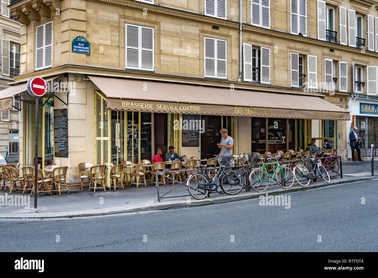 Bicycles against a railing  outside the Bo Man cafe and restaurant , Rue Notre-Dame-de-Lorette , Paris,France Stock Photo
