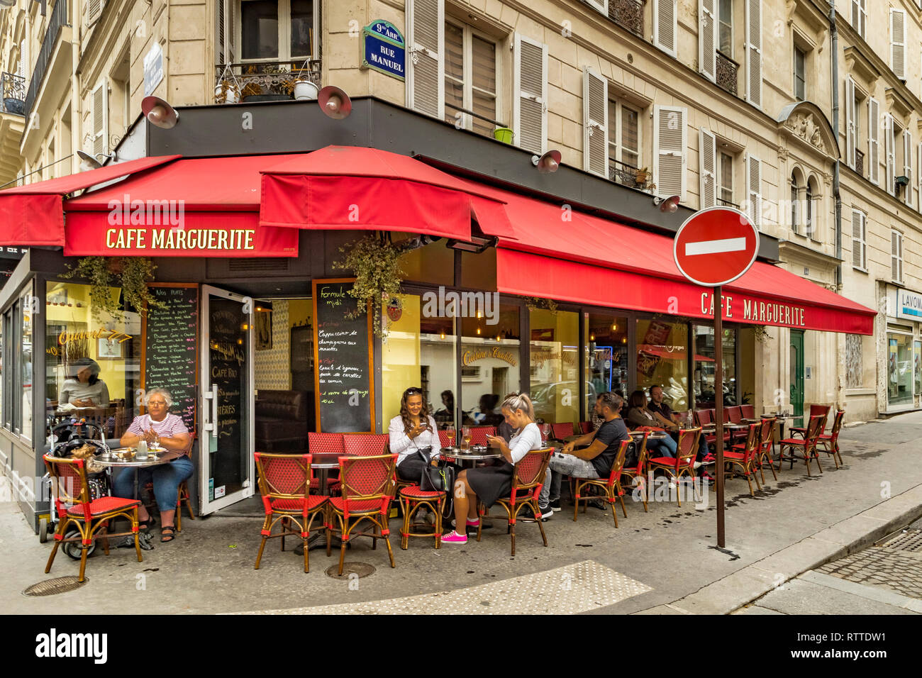 Two girls looking at their mobile phones sitting outside Cafe Marguerite Rue des Martyrs ,St Georges  in the 9th arrondissement of Paris Stock Photo