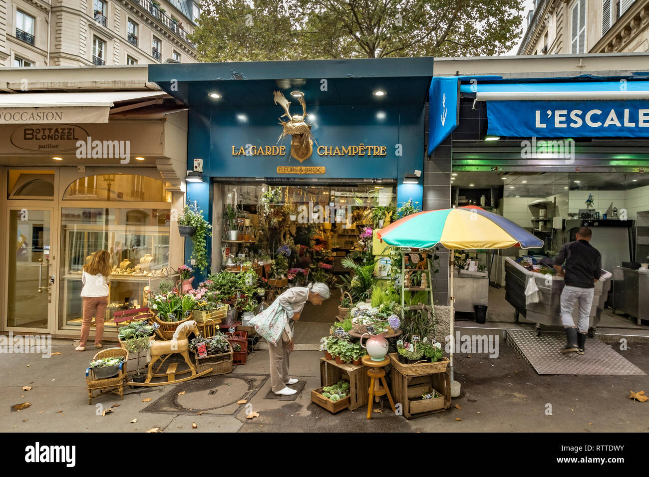 A woman looking at the flower displays at La Garde Champêtre ,a florist shop and flower seller on Rue des Martyrs , St Georges ,Paris - Stock Image