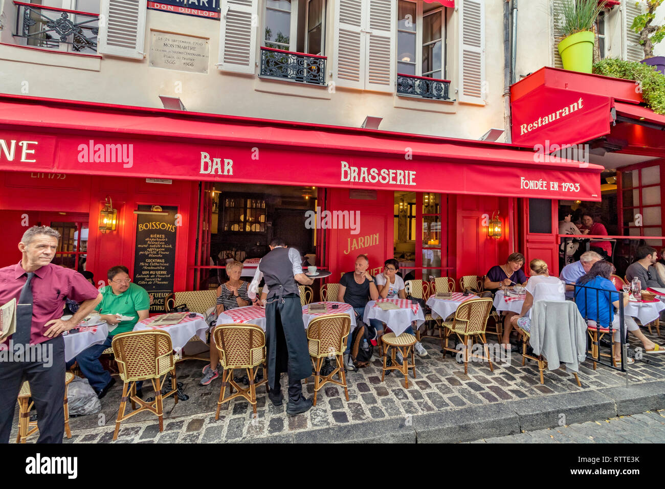 A waiter serving a customer at La Mère Catherine,the oldest restaurant in Place du Tertre ,Montmartre,Paris - Stock Image