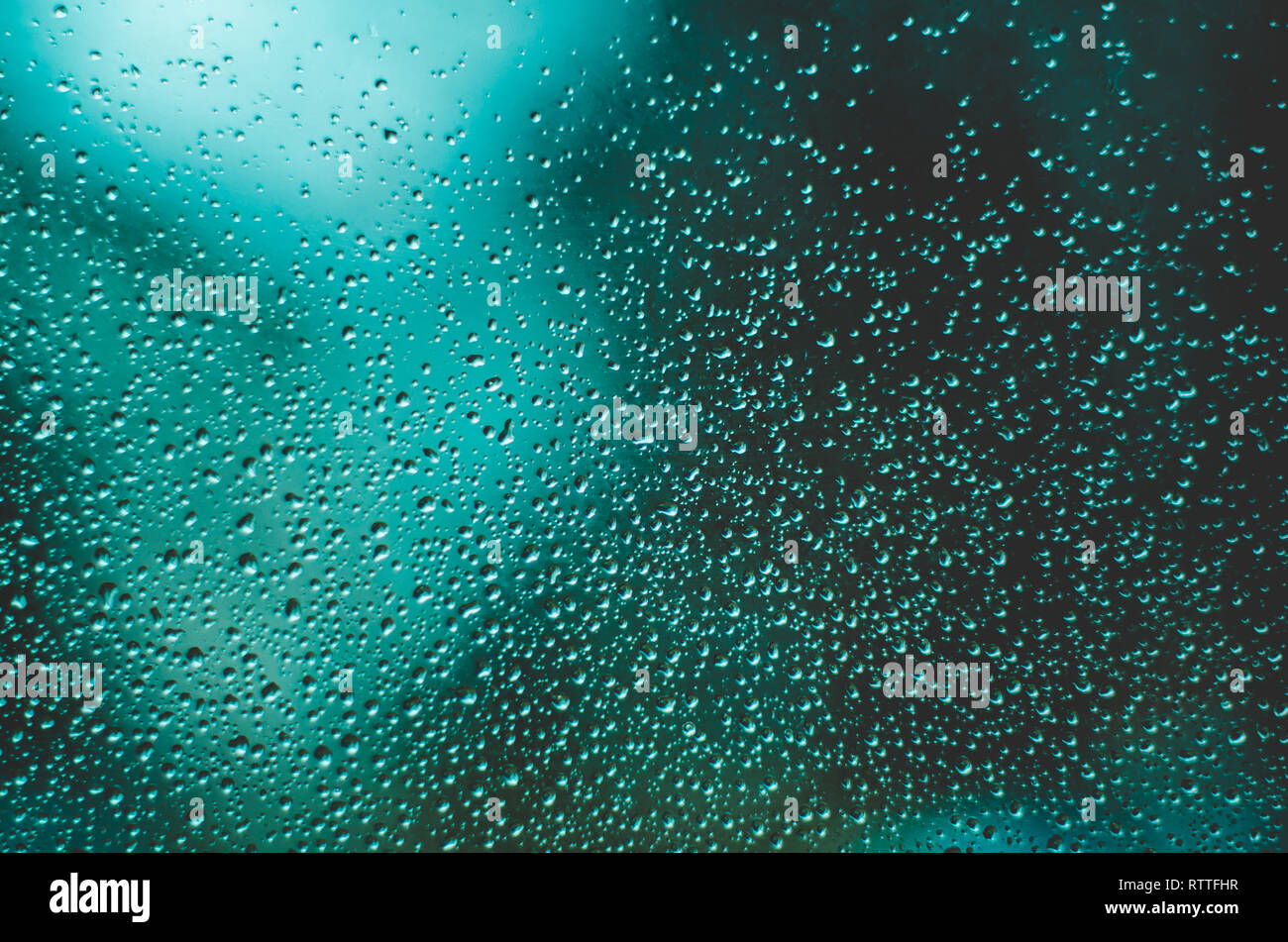 Water Drops On Windows Close Up Against Blurry Dark Teal Background Stock  Photo - Alamy