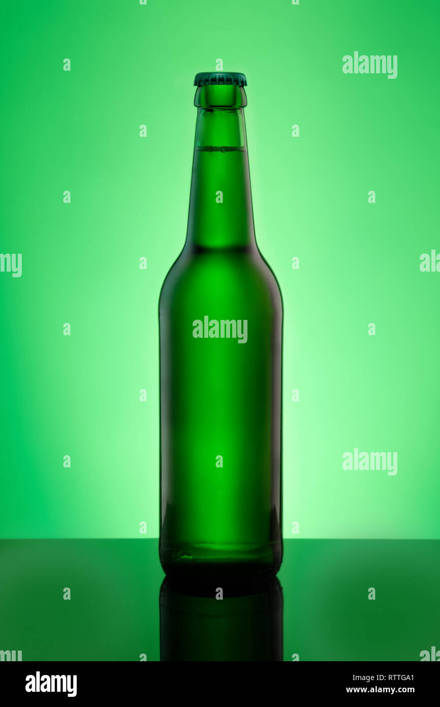 Green beer bottle with crown cap in vertical format in back lit - Stock Image