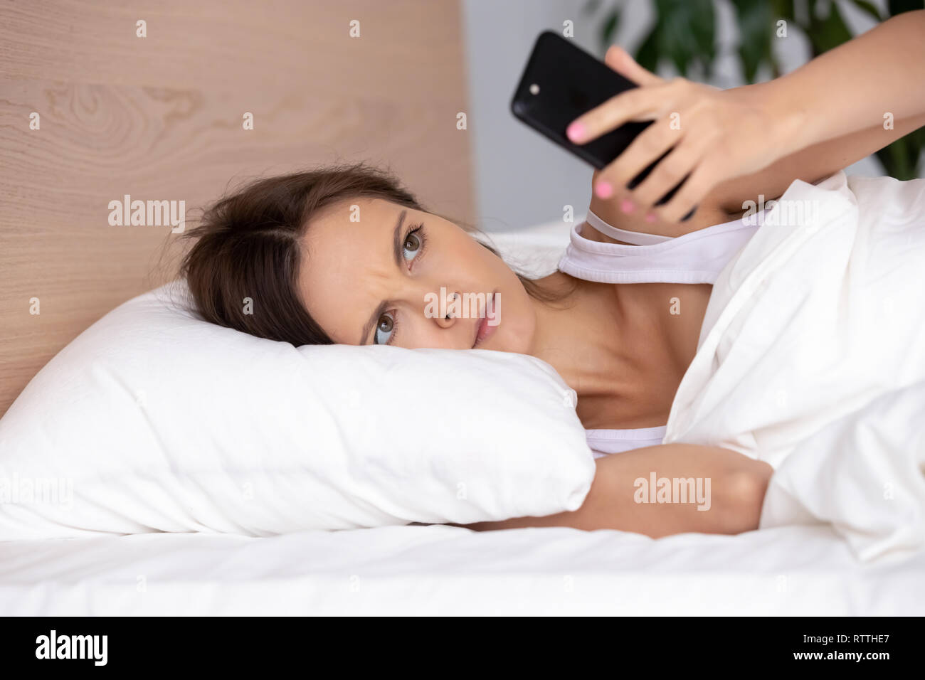 Upset young woman using phone in bed, looking at screen, insomnia - Stock Image