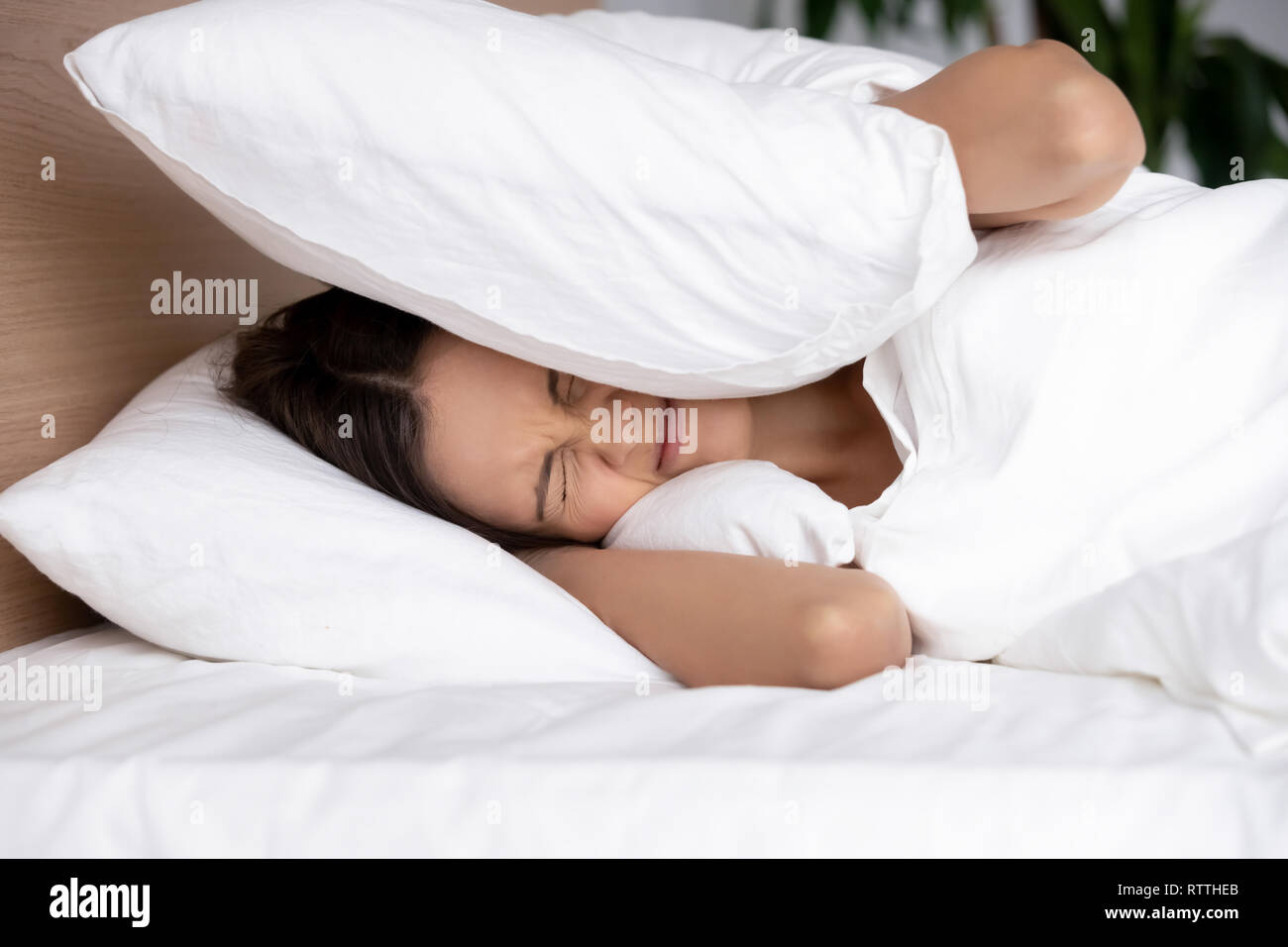 Annoyed young woman covering ears with pillow, suffering from noise - Stock Image