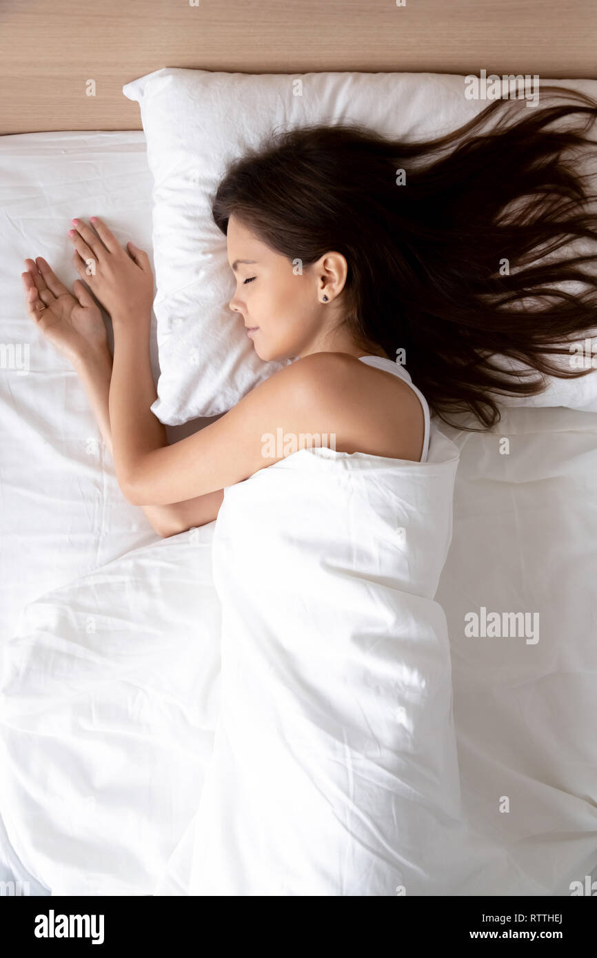 Vertical, beautiful young woman sleeping in comfortable bed - Stock Image