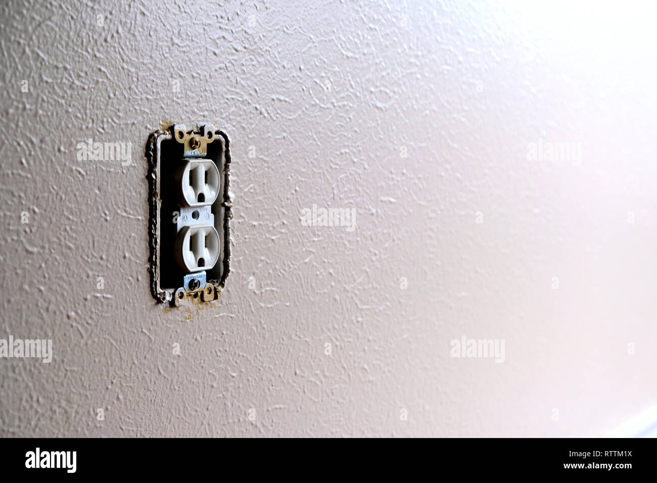 Interior unprotected wall socket; American electrical outlet missing a wall plate. - Stock Image