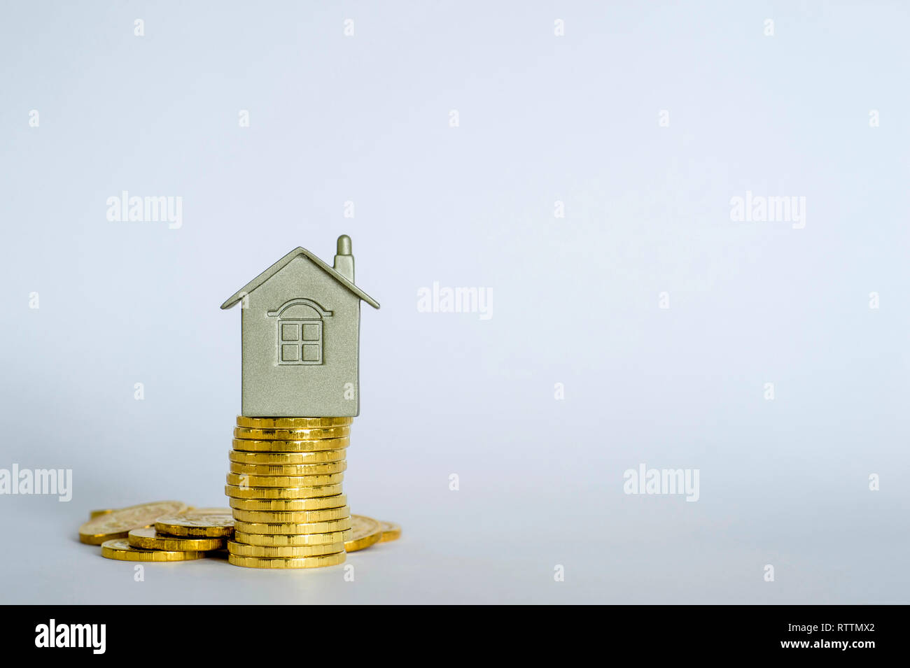 The house symbol on a stack of yellow shiny coins on a light gray blue background. Real estate purchase offer concept. Copy space. - Stock Image