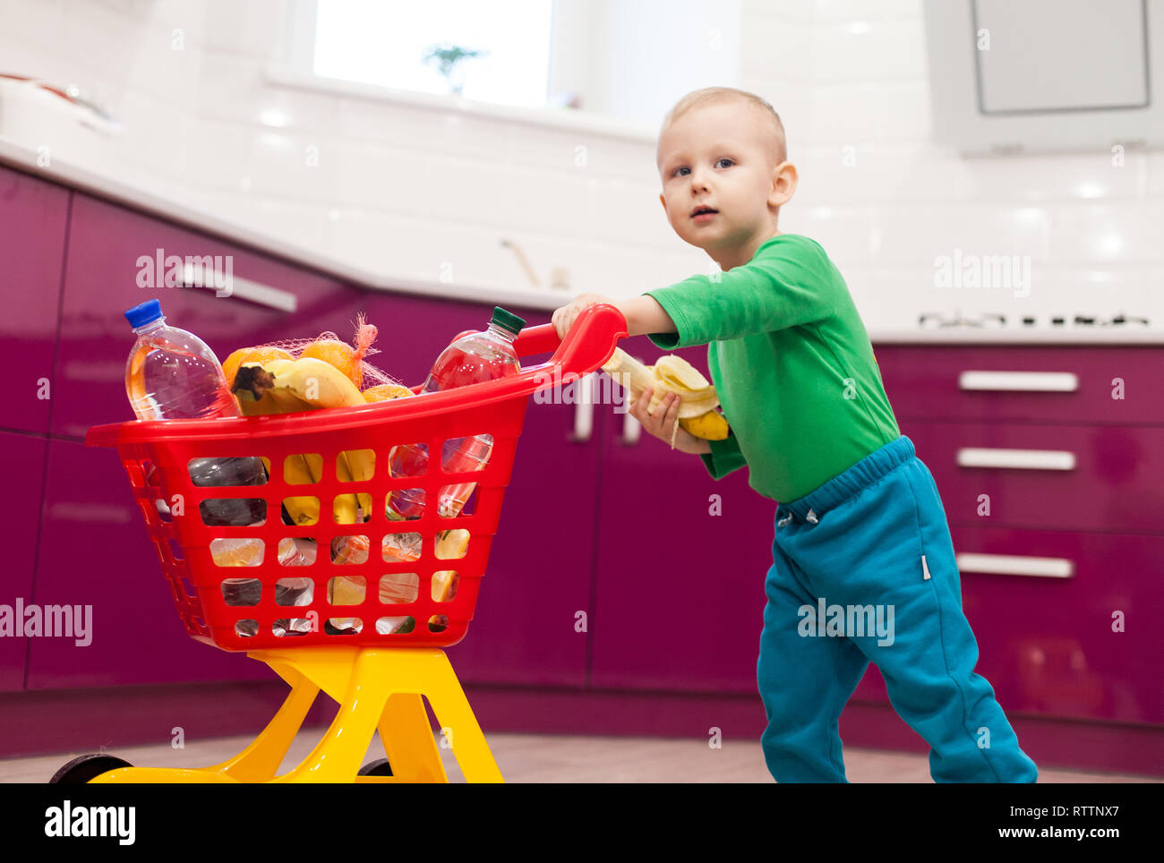 Cheerful little boy with shopping cart. Little kid in casual wear carrying child plastic shopping trolley. Shopping, discount, sale concept - Stock Image