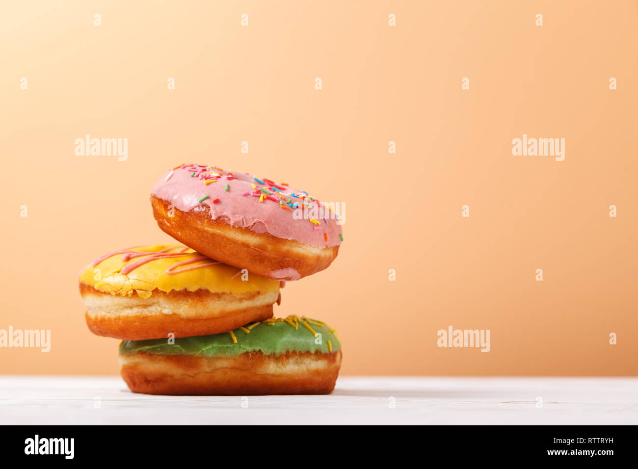 three appetizing multi colored donuts on a plain background of beige peach color copy space the concept of serving sweets in the bakery hanukkah ba stock photo alamy https www alamy com three appetizing multi colored donuts on a plain background of beige peach color copy space the concept of serving sweets in the bakery hanukkah ba image239032181 html