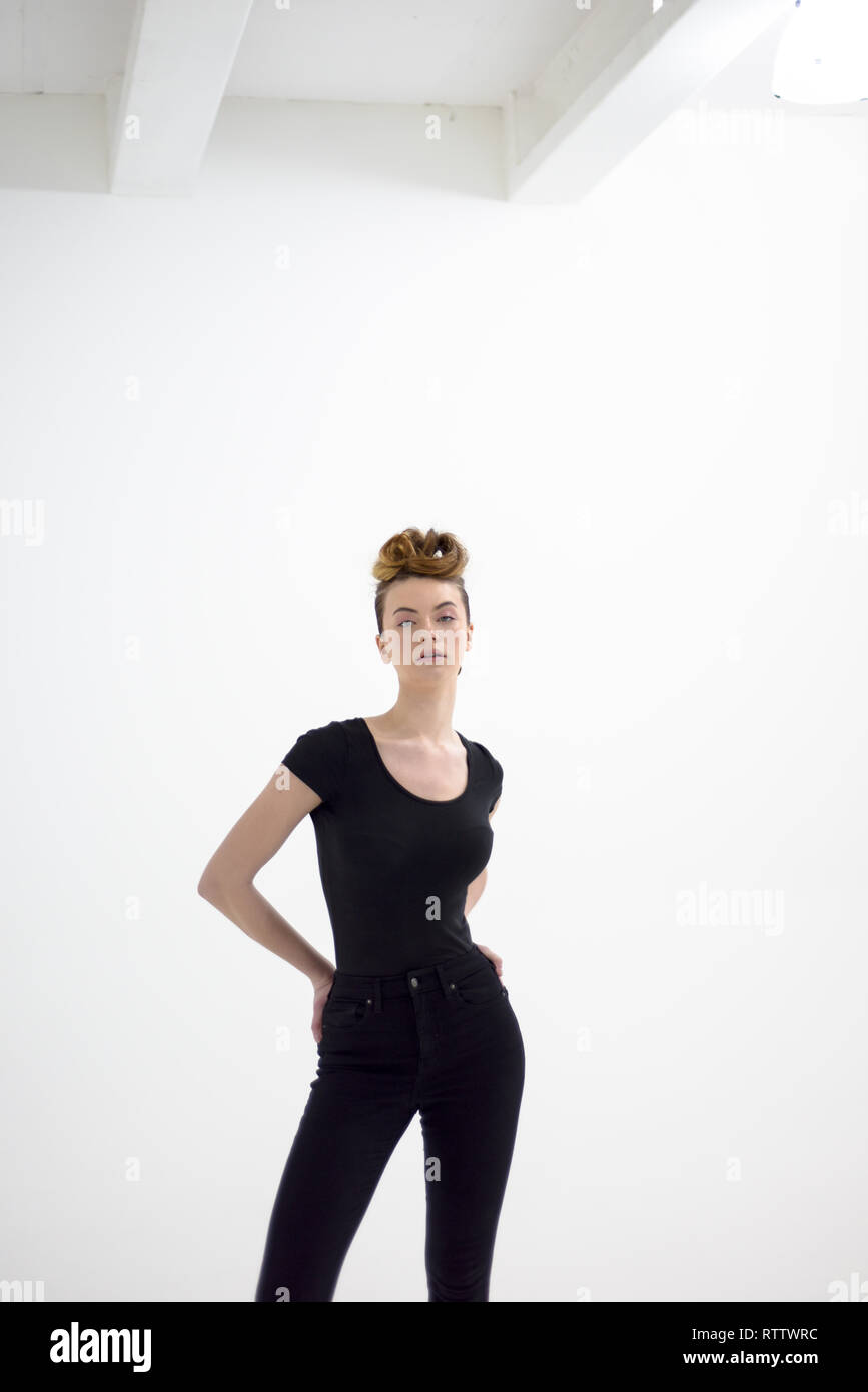 A Beautiful High Fashion Model Poses In A Predominantly White Space And Is Wearing Black Jeans And A T Shirt She Has Her Hair Up And Is Very Cool Stock Photo Alamy