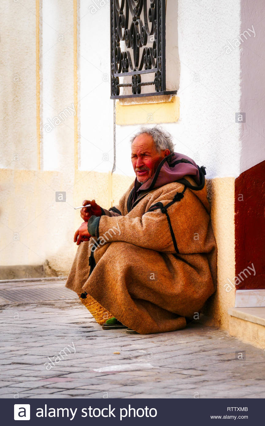 Tunesia, Sousse,03/20/2015: Old man sits  at the entrance on the street in Sousse  smoking a cigarett - Stock Image