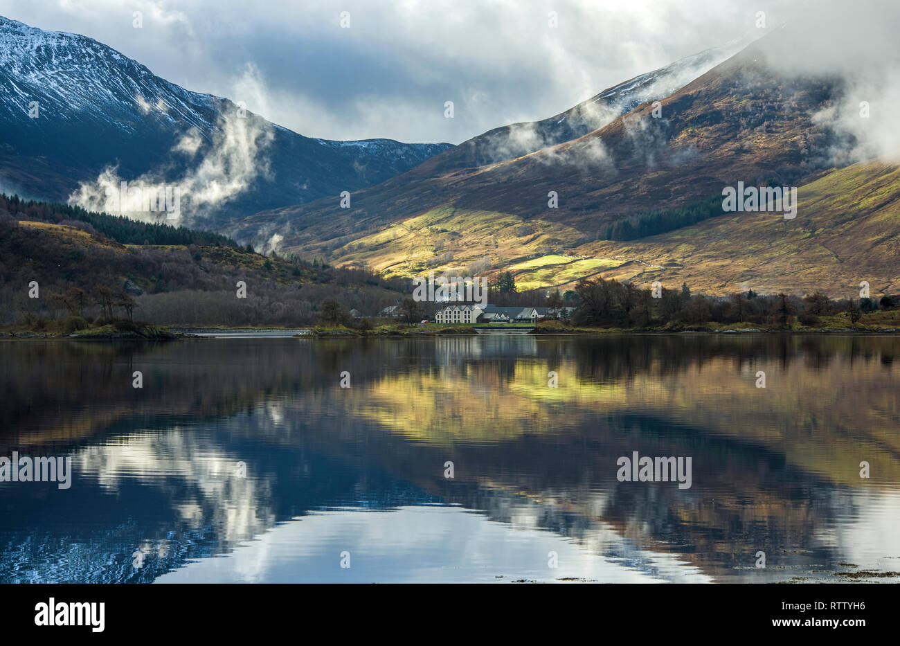 Clear reflections of the mountains and trees on Loch Leven, Glencoe, on a beautifully lit winter day in February. Stock Photo