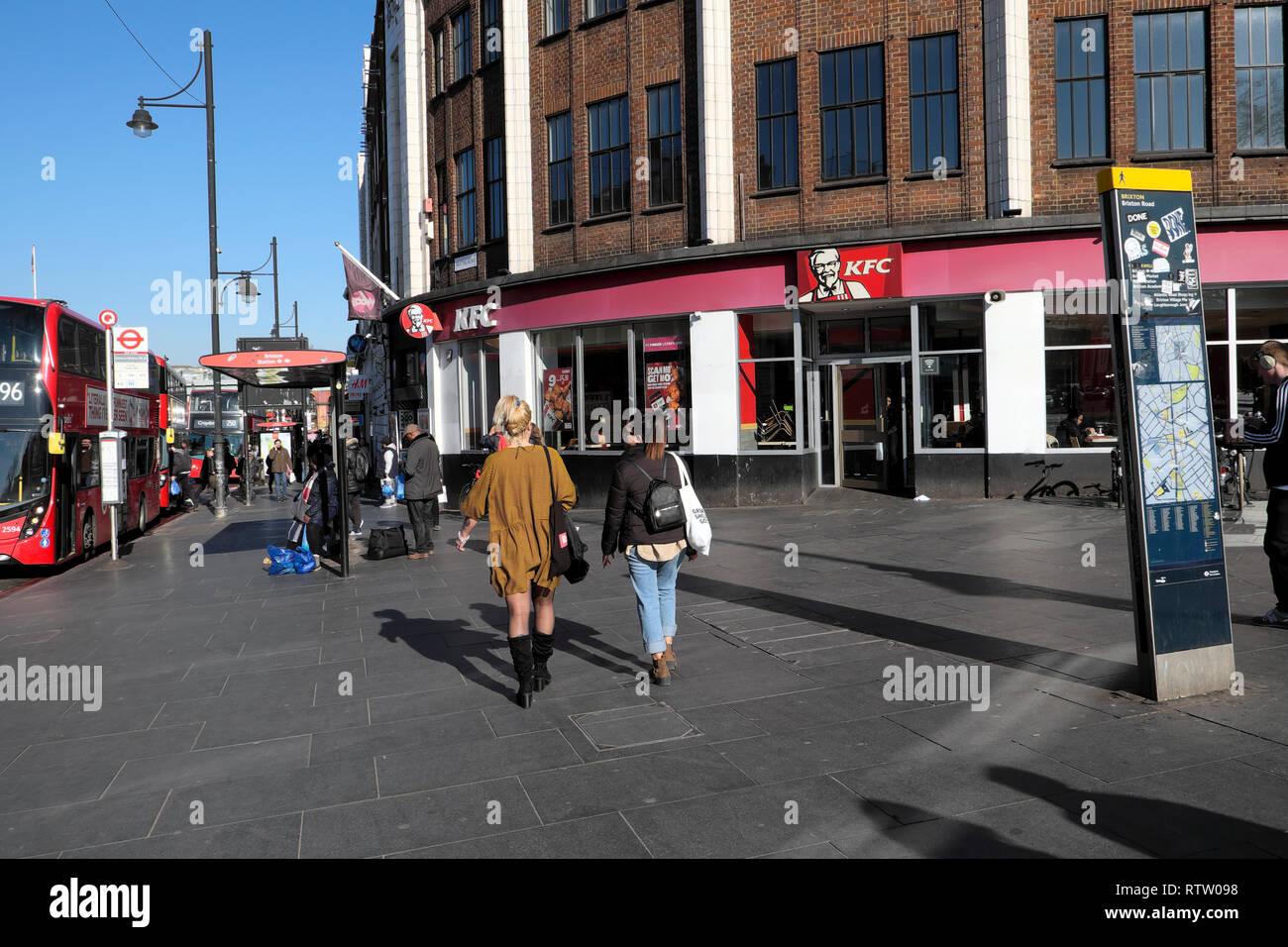 Rear view of women walking past KFC Kentucky Fried Chicken restaurant on Brixton Road in Brixton, Borough of Lambeth, South London UK   KATHY DEWITT - Stock Image