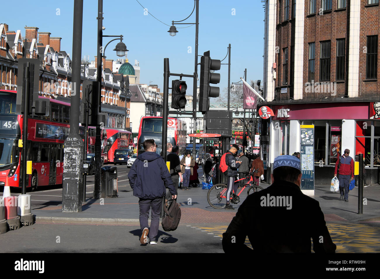 People walking along busy Brixton Road crossing the street at traffic lights and buses in Brixton, Borough of Lambeth, South London UK   KATHY DEWITT - Stock Image