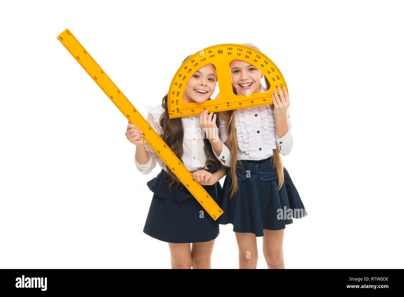 Having fun in school. Pupil cute girls with big rulers. School children with measuring instruments. Geometry favorite subject. Education and school concept. School students learning geometry. - Stock Image