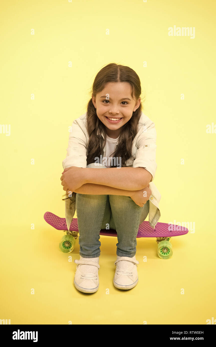 88e2d94cb25f Happy girl sit on penny board on yellow background. Little child smile with  long hair