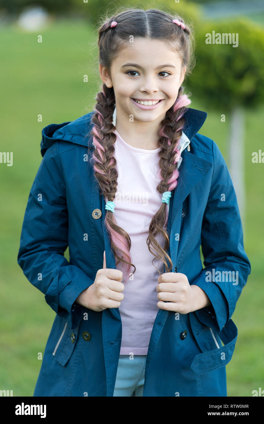 Spring coat. Must have concept. Fashionable coat. Girl cute face braided hair posing coat in spring park. Clothing for spring walks. Little fashion model. Clothes and accessory. Kid wear trench coat. - Stock Image