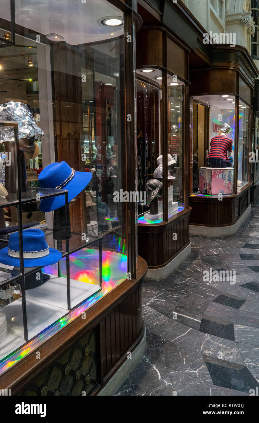 Hat shop window display showing a rainbow effect in the reflections in Burlington Arcade, London, UK - Stock Image