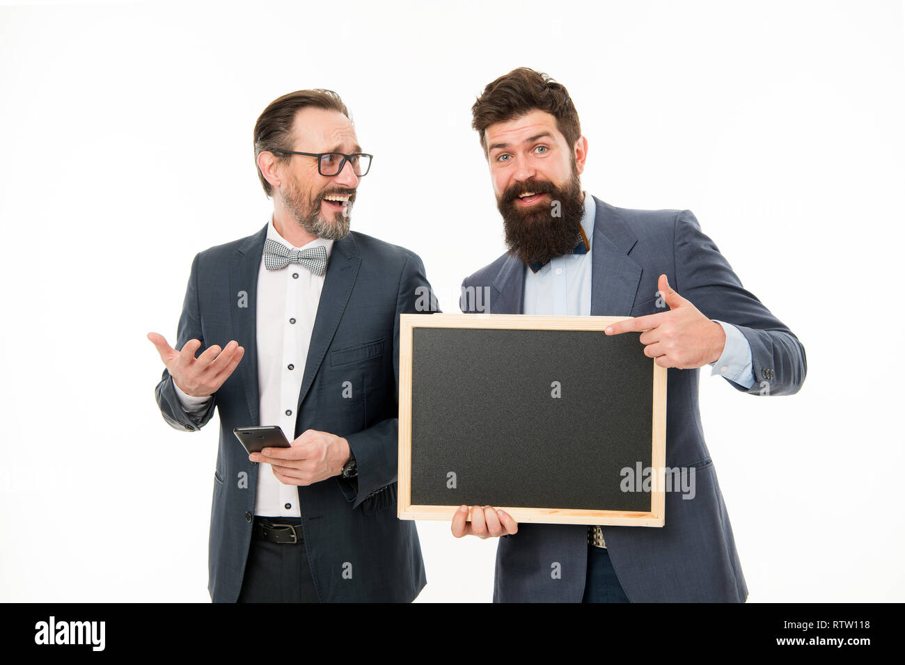 Conference timing. Men successful entrepreneurs on white background. Join our business team. Business people concept. Men bearded guys wear formal suits. Well groomed business man hold chalkboard. - Stock Image