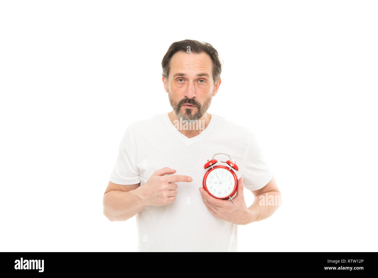 What time is it. Time management and discipline. Punctuality and responsibility. Man with clock on white background. Check time. Man hold alarm clock in hand. Guy bearded mature man worry about time. - Stock Image