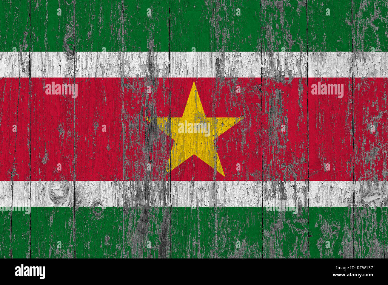 Flag of Suriname painted on worn out wooden texture background. - Stock Image