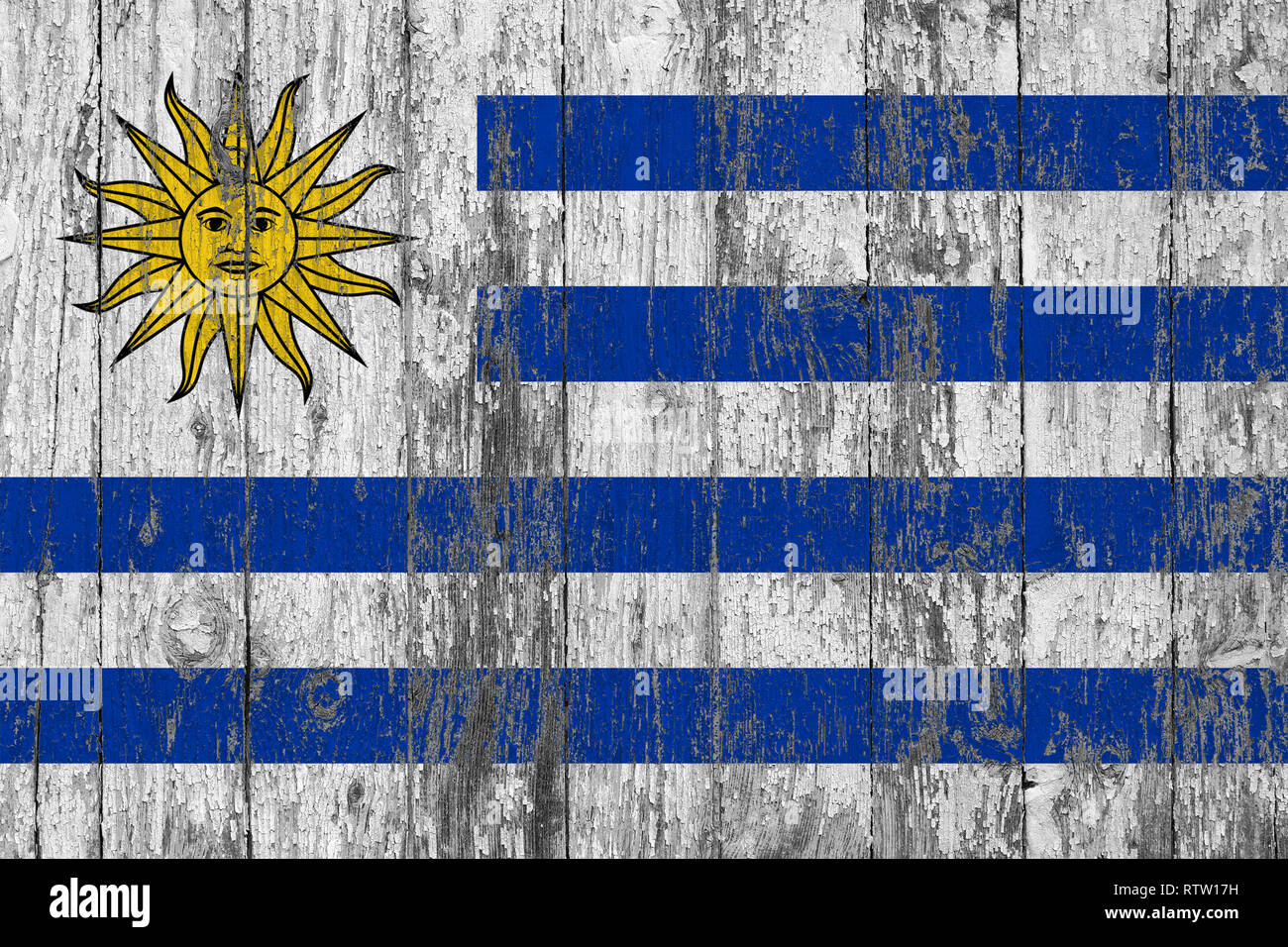 Flag of Uruguay painted on worn out wooden texture background. - Stock Image