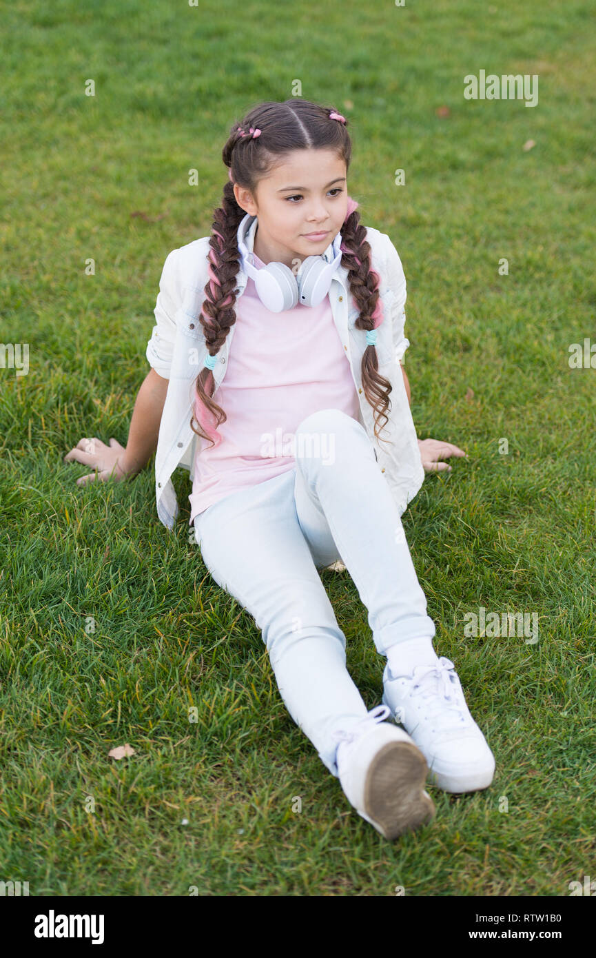 Girl cute kid green grass background. Healthy emotional happy kid relaxing outdoors. What makes child happy. Girl braids hairstyle and modern headphones enjoy relax. Secrets to raising happy child. - Stock Image