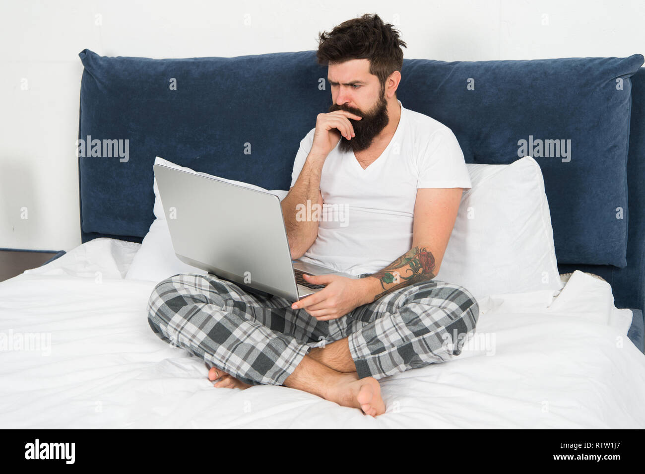 Freelance job. Stay in bed and keep working. Freelance benefits. Man surfing internet or working online. Hipster bearded guy pajamas freelance worker. Remote work concept. Online search job position. - Stock Image