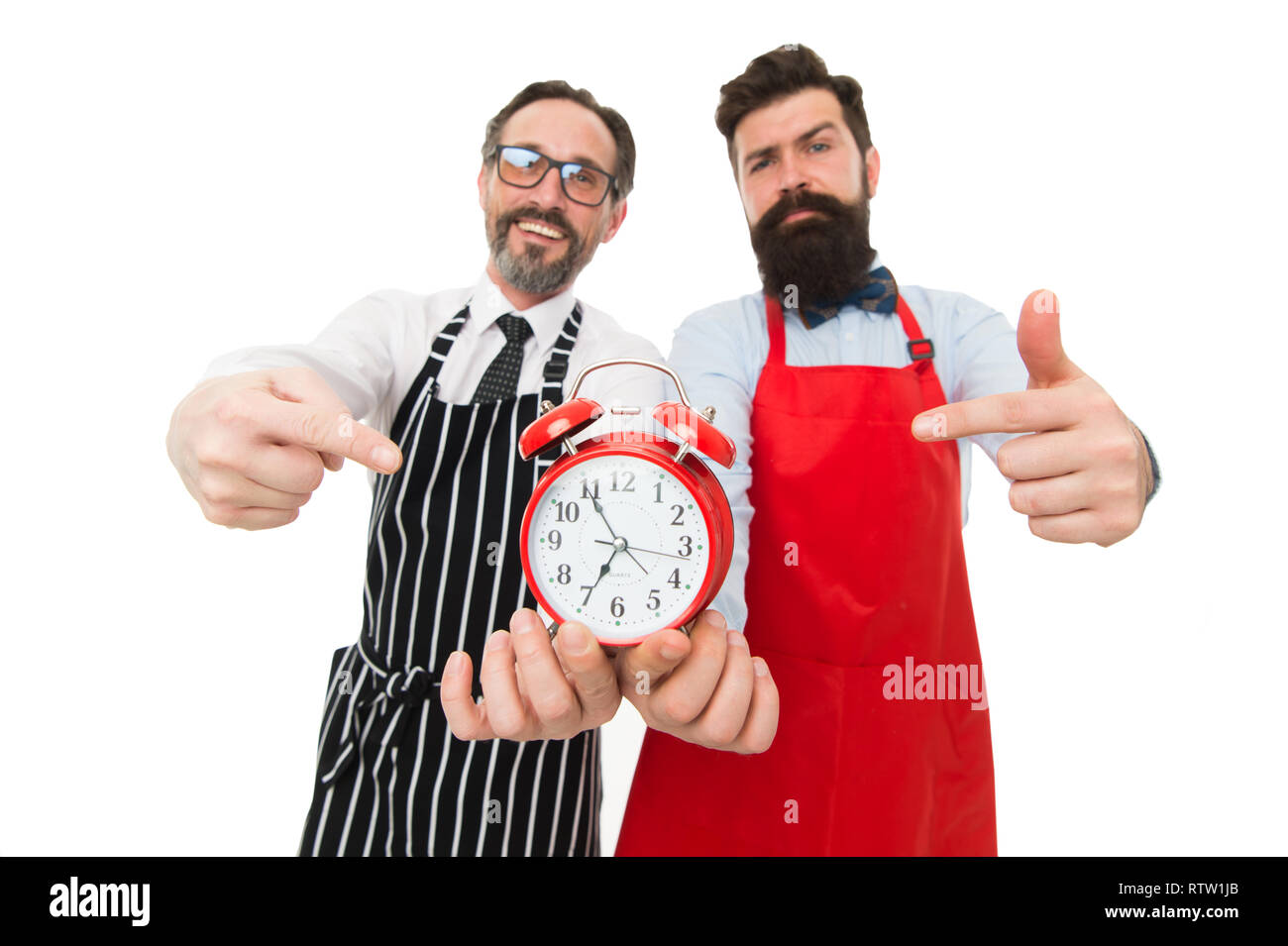 Time to cook. Men pointing at alarm clock. Man bearded hipster and mature chef apron white background. Cook dinner. We going to cook right now. Friends colleagues start cooking just on time. - Stock Image