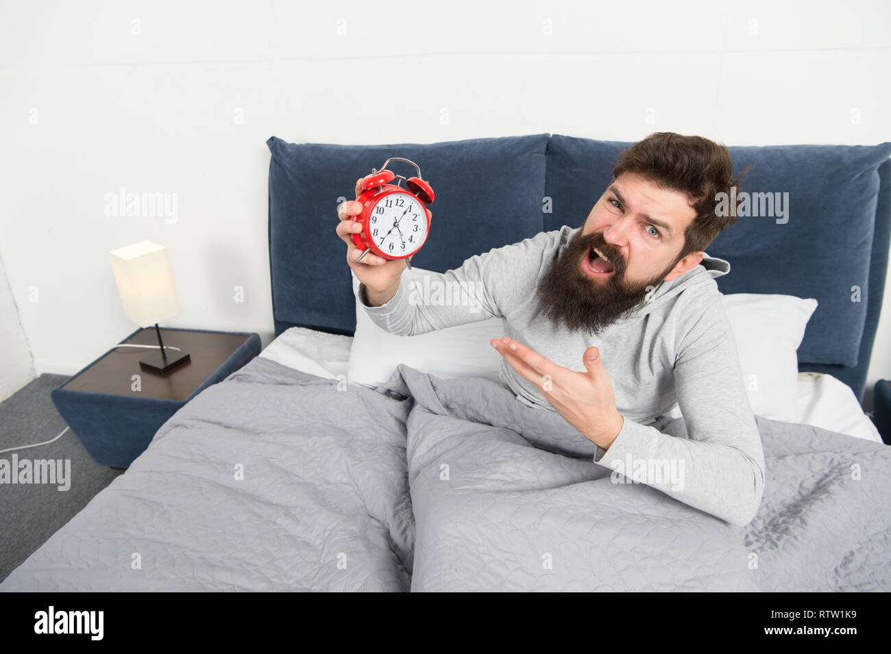 Get up early. Tips for waking up early. Man bearded hipster sleepy face waking up. Daily schedule for healthy lifestyle. Alarm clock ringing. Hate this noise. Problem with early morning awakening. - Stock Image