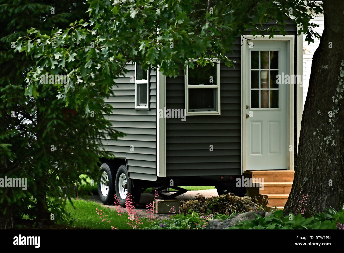 Closeup exterior view of an affordable eco friendly tiny house on wheels - Stock Image