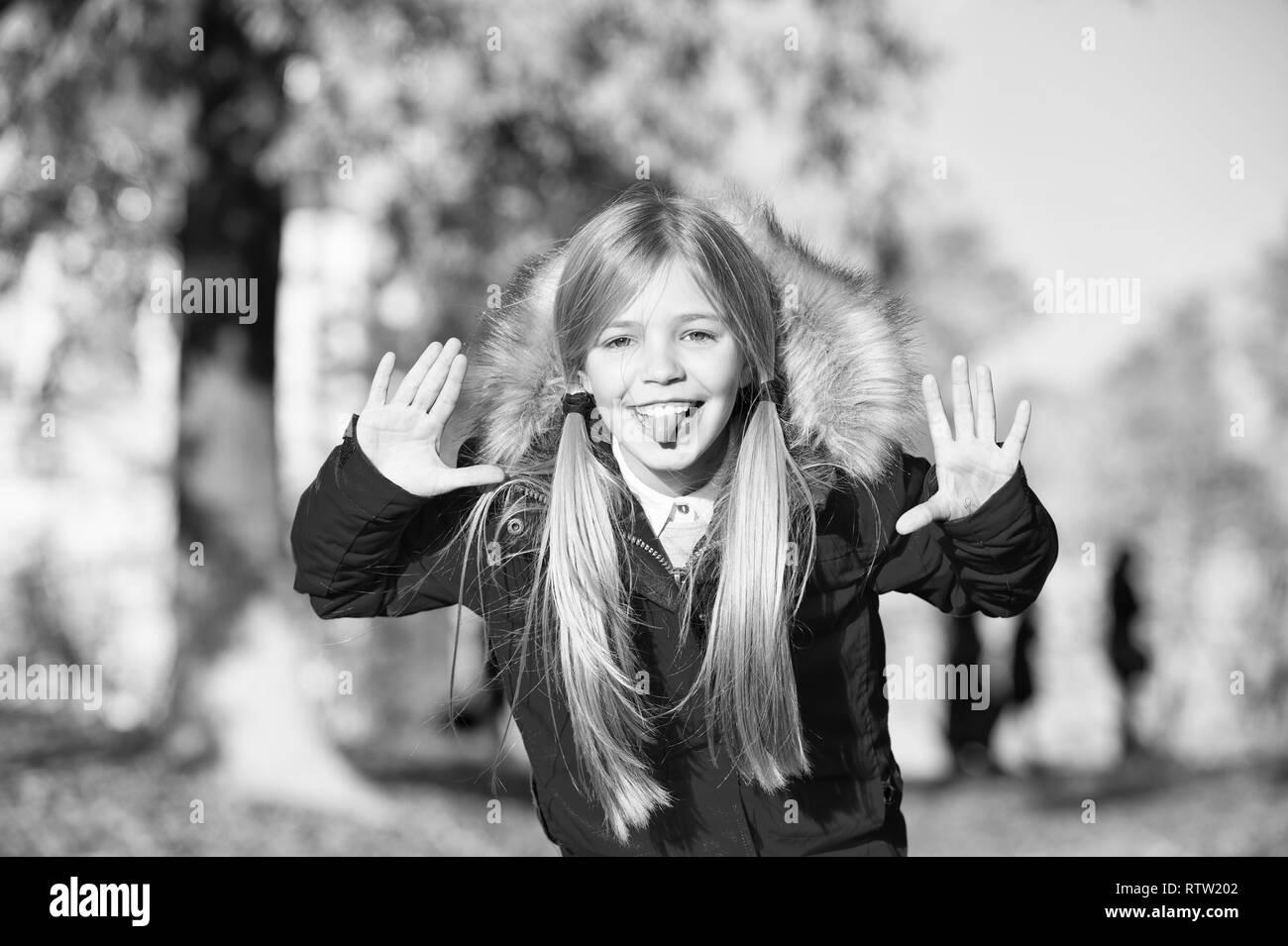 f1b196745 Girl playful grimace face in coat enjoy fall park. Playful kid ...