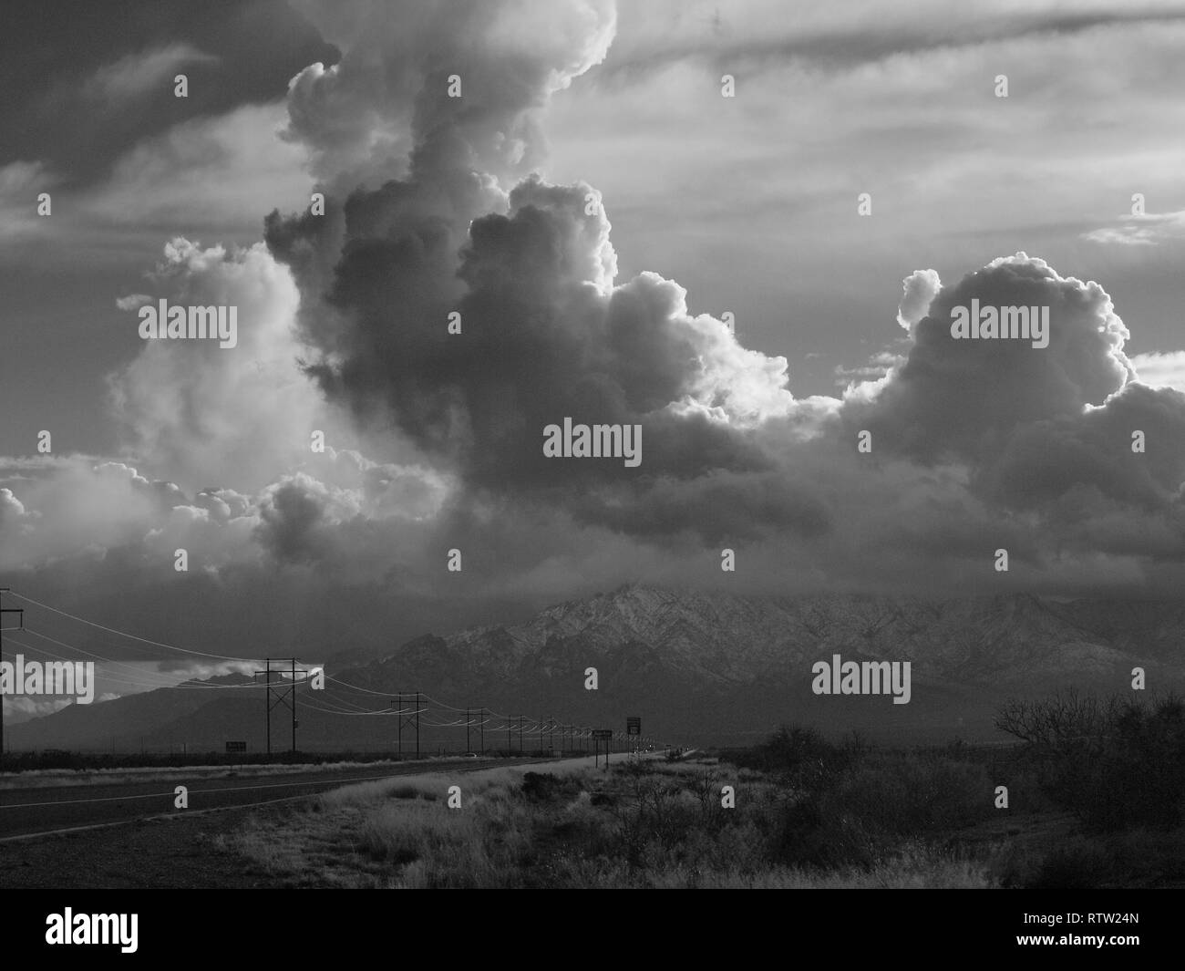 Huge billowing clouds over US 70 in New Mexico towering over mountains in black and white. Powerlines march toward the horizon. - Stock Image