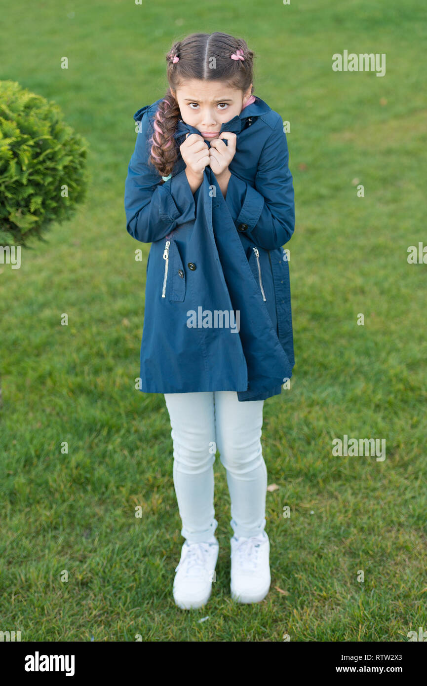 Girl cute face braided hair posing coat in spring park. Clothing for spring walks. Little fashion model. Clothes and accessory. Kid wear trench coat. Spring coat. Must have concept. Fashionable coat. - Stock Image