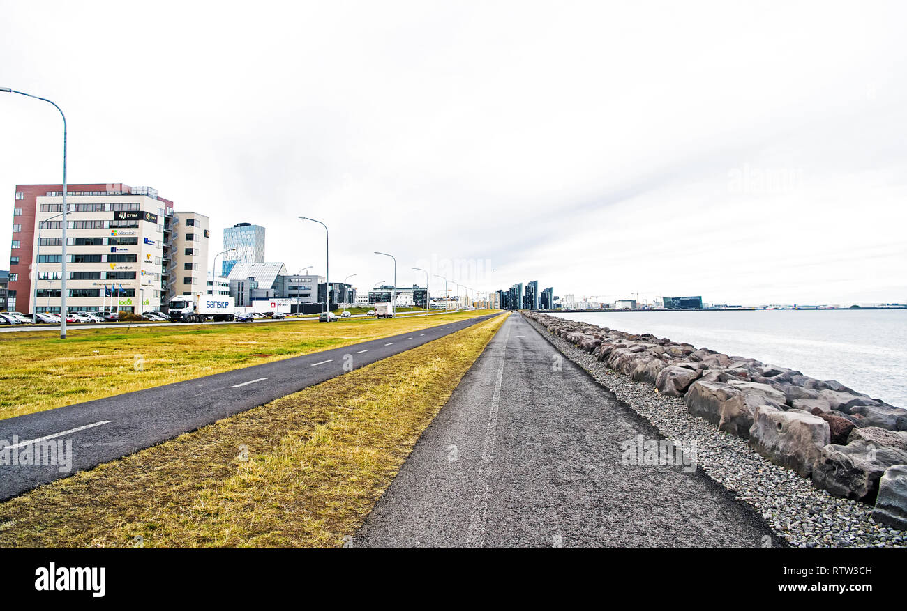Reykjavik, Iceland - October 12, 2017: city roads along sea on cloudy sky. Promenade at seaside. Freedom, perspective and future. Travel and wanderlust on urban landscape. - Stock Image