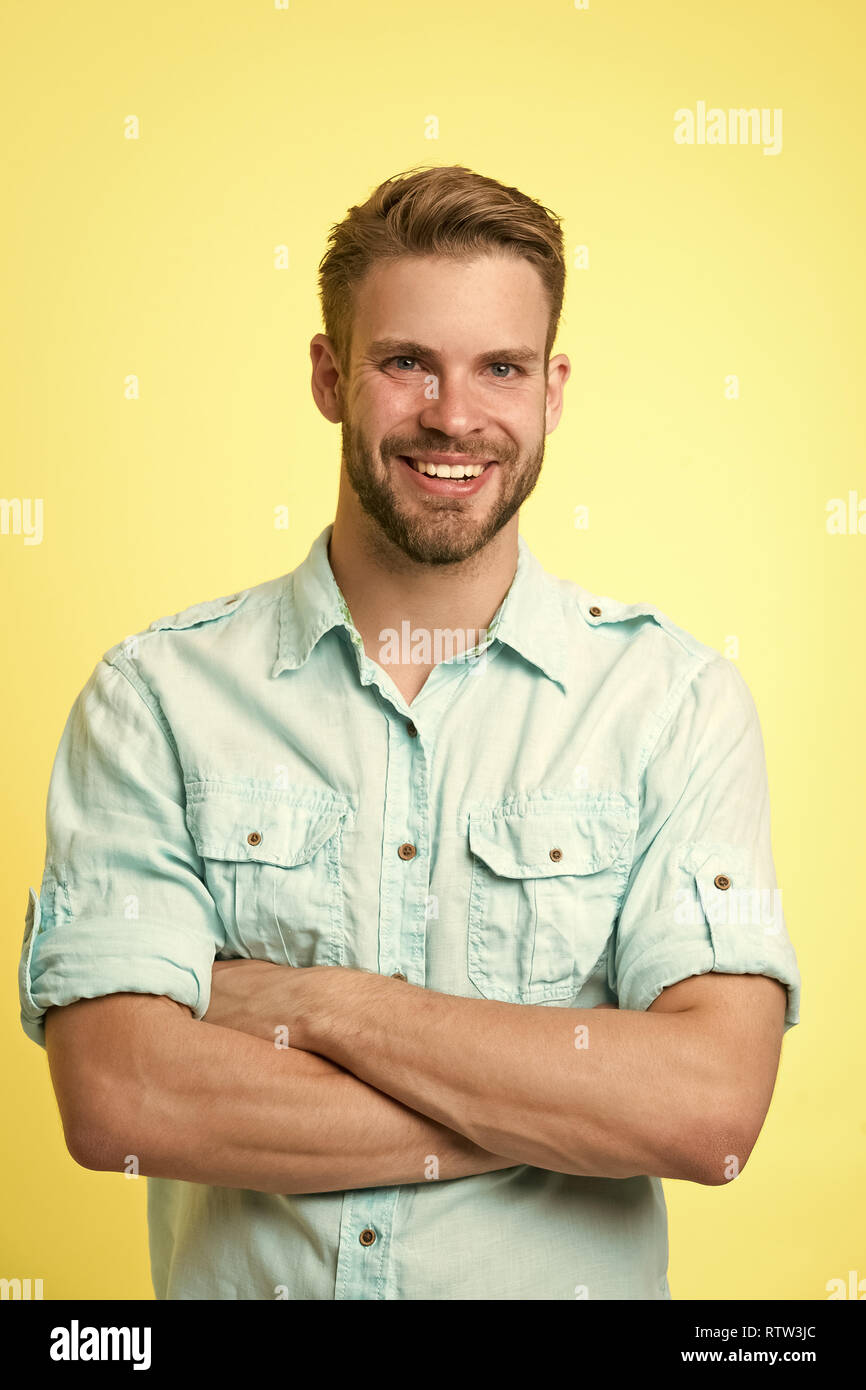 Cheerful consultant. Man smiling face posing confidently with folded arms yellow background. Man shop consultant looks cheerful confident and hospitable. Guy with bristle glad to help you in shop. Stock Photo