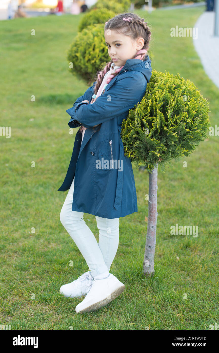 Must have concept. Fashionable coat. Girl cute face braided hair posing coat in spring park. Clothing for spring walks. Little fashion model. Clothes and accessory. Kid wear trench coat. Spring coat. - Stock Image