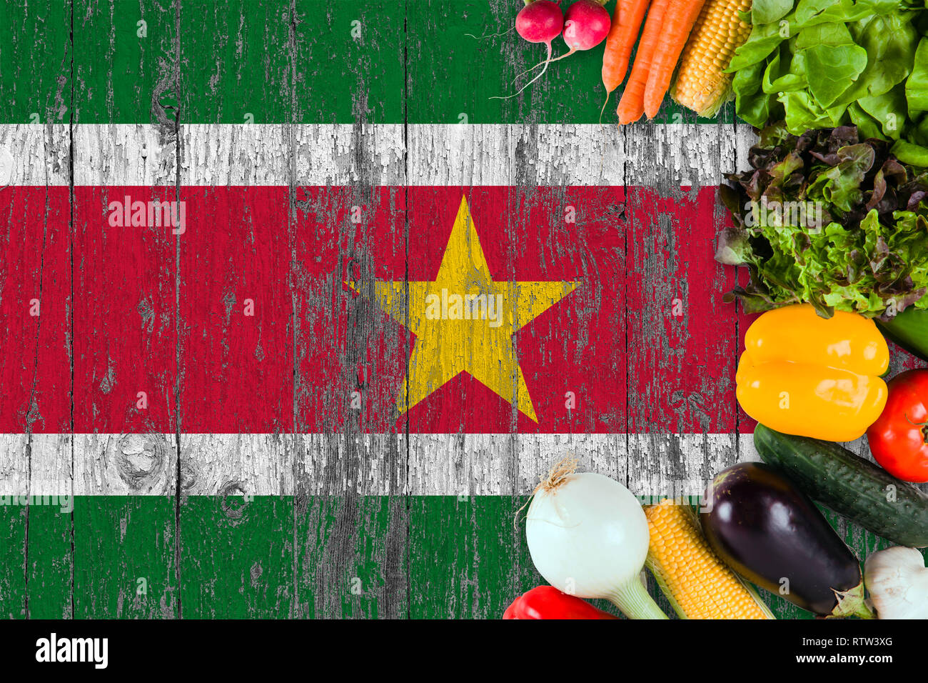 Fresh vegetables from Suriname on table. Cooking concept on wooden flag background. - Stock Image
