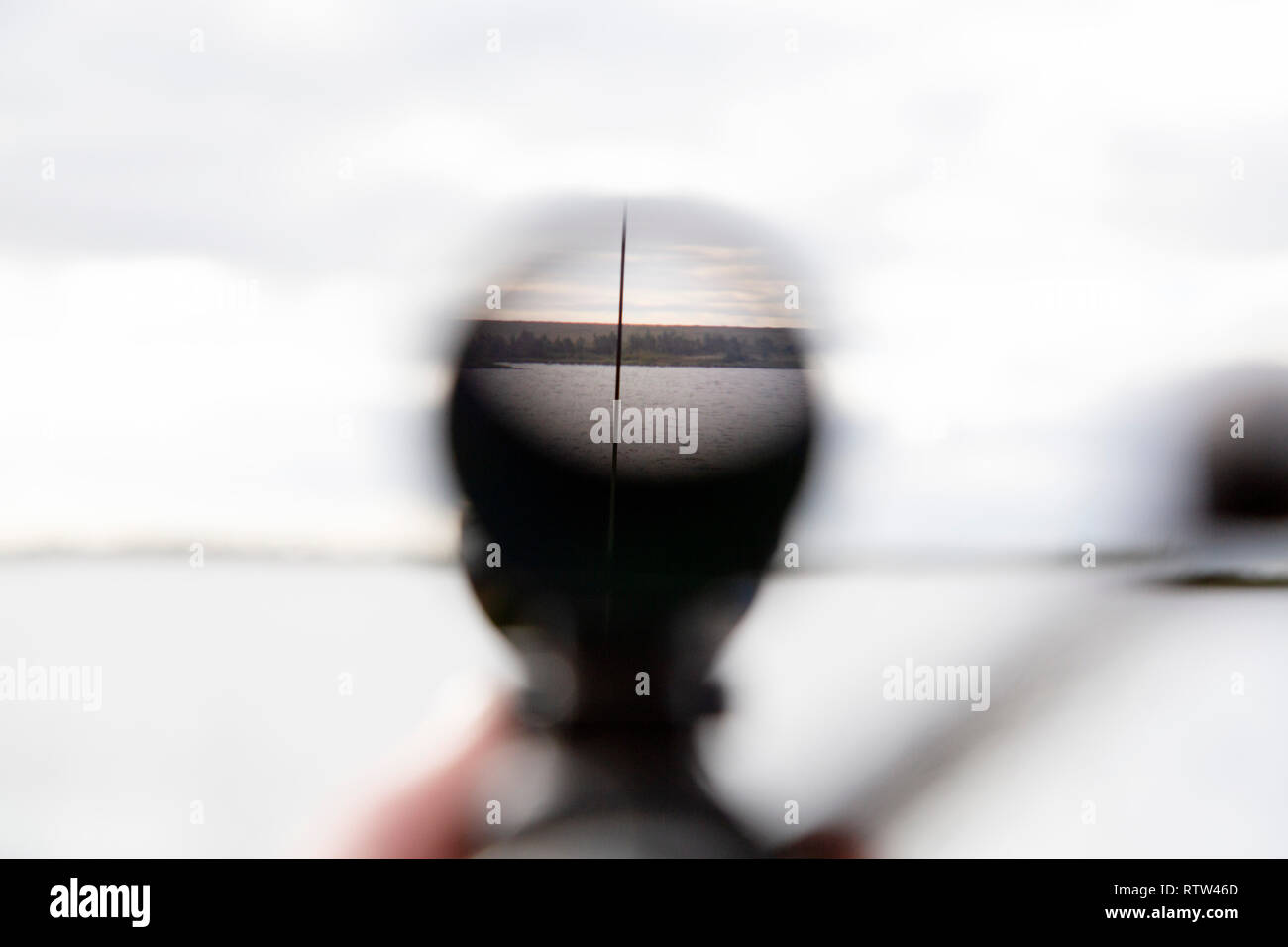 View through the telescopic sight of a hunting rifle. The rifle points into the distance. - Stock Image