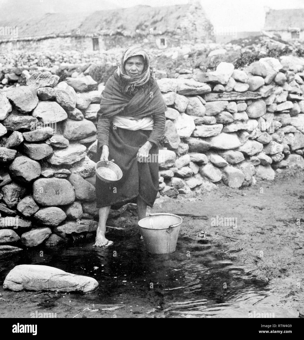 irish peasant woman collecting water in the west coast of ireland circa 1900  Image updated using digital restoration and retouching techniques - Stock Image