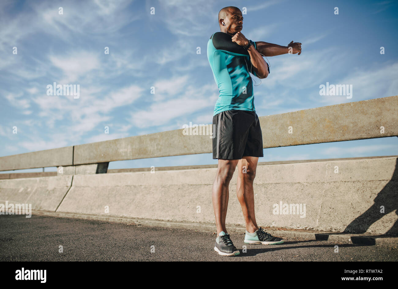 African american man in sportswear stretching his arms. Male athlete warming up before a run in morning in city. - Stock Image