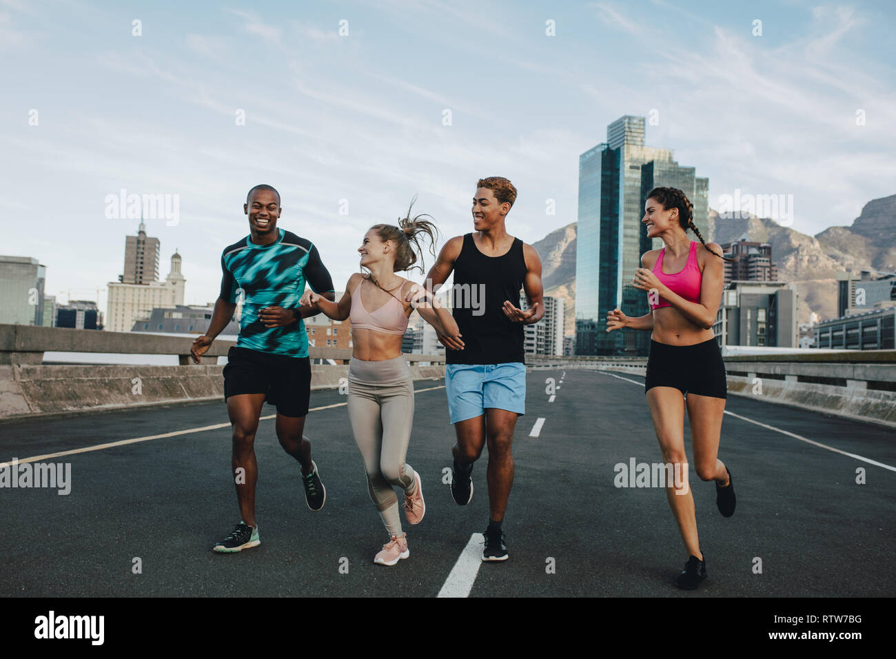 Healthy young people running together in morning on street. Runners training together outdoors in morning. - Stock Image