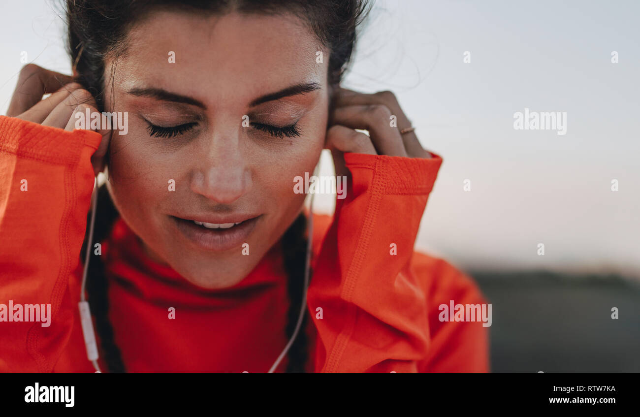Close up of sportswoman adjusting her earphones during a workout break. Female runner listening to music on earphones during break outdoors. - Stock Image