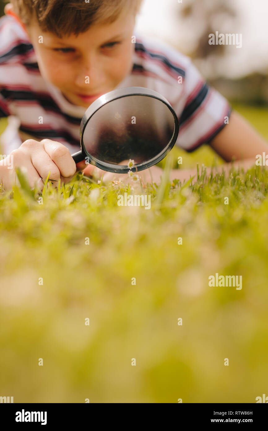 Kid playing with magnifying glass outdoors. Boy exploring garden using magnifying glass at the park. - Stock Image