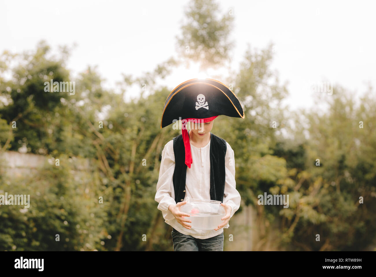 Boy dressed up as pirates walking with fish bowl outdoors. Boy playing as pirates outdoors. - Stock Image