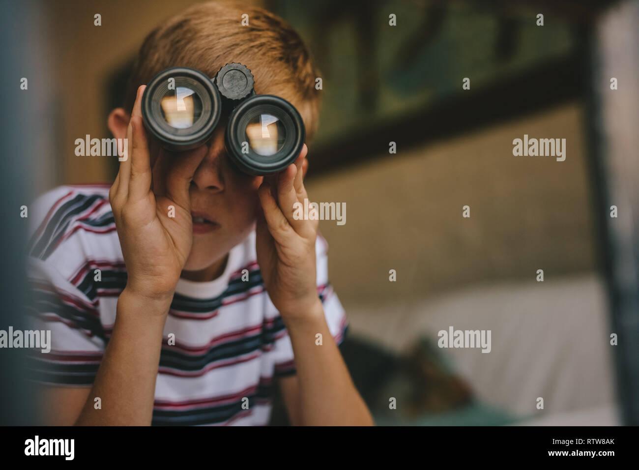 Small boy looking outside window using binoculars. Boy looking through binoculars from the living room. - Stock Image