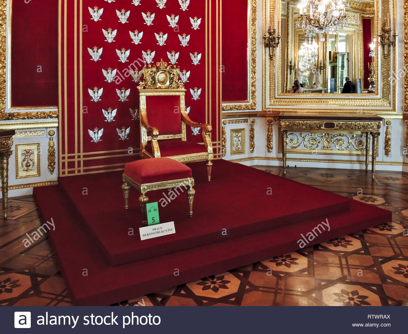 The throne and footstool in the Throne Room of the Royal Castle in Warsaw, Poland, with a mirror reflecting chandeliers - Stock Image