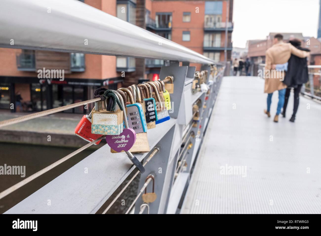 Embracing couple walk past Lovelocks or love locks padlocked on to a bridge in Birmingham, England, GB, UK. Stock Photo