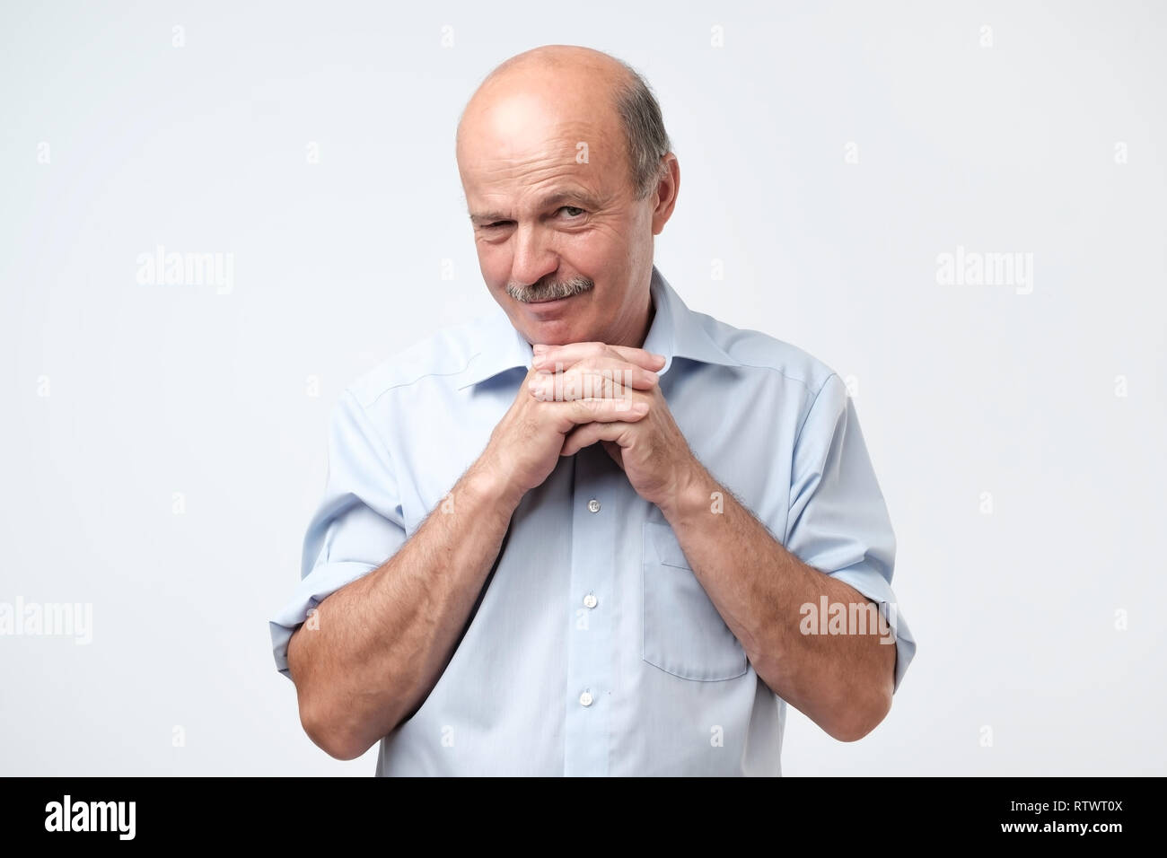 Cunning tricky mature man thinking looking with hand together over gray background. Concept of unfair game - Stock Image