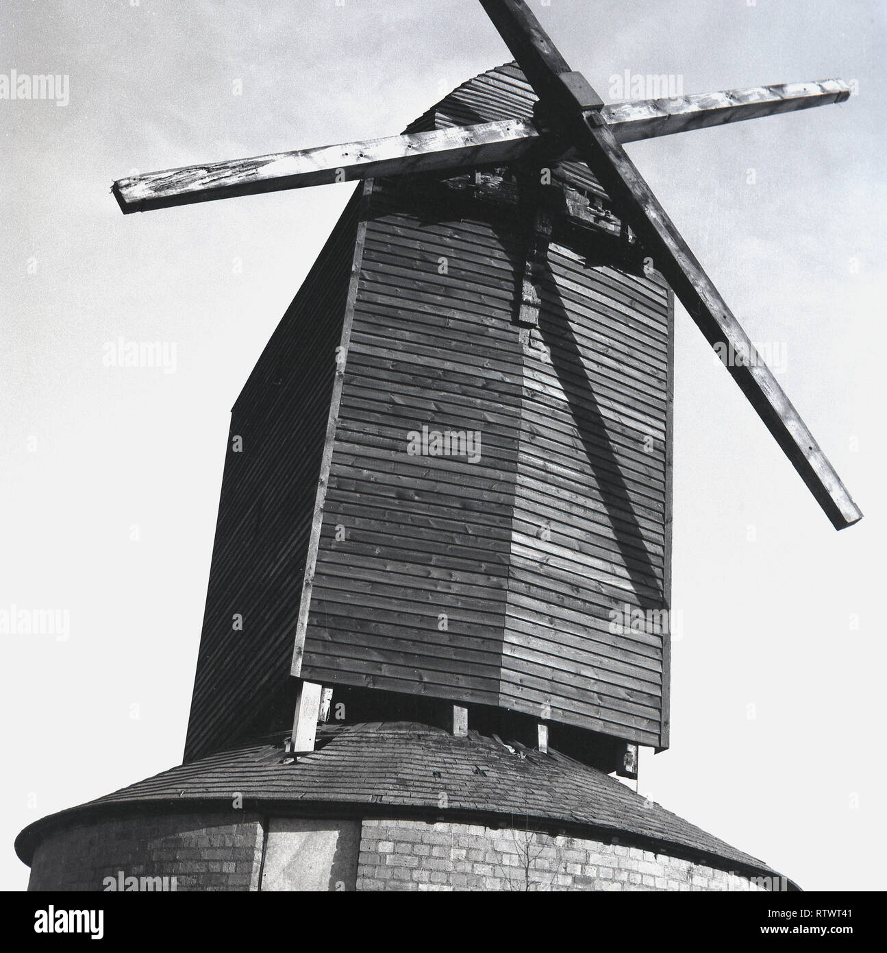 1970s, the Brill Windmill, Bucks, England. A traditonal windmill, the picture shows the plain, basic 'post mill' here with wooden vanes or blades and a wooden clapper board 'post' fixed onto the mill's main structure or body. This kind of 'post mill' is considered the earliest type of European windmill and is so named as the large upright post is balanced on the main structure or trestle surrounded as seen here by a roundhouse to protect the trestle from the weather and to provide storage space. - Stock Image